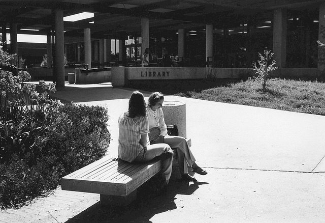 photo of the outside of the library with two young women sitting in front.