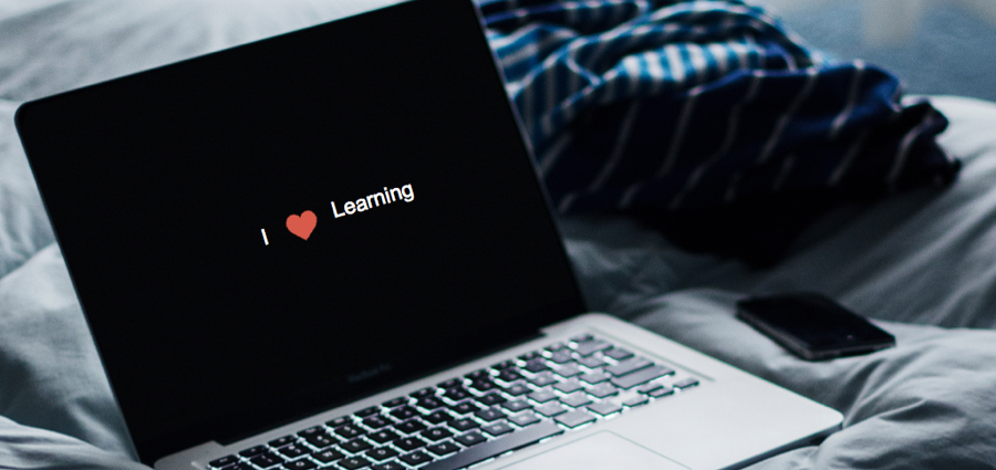 "Header graphic of a laptop on a bed with the words ""I heart (symbol) learning"""